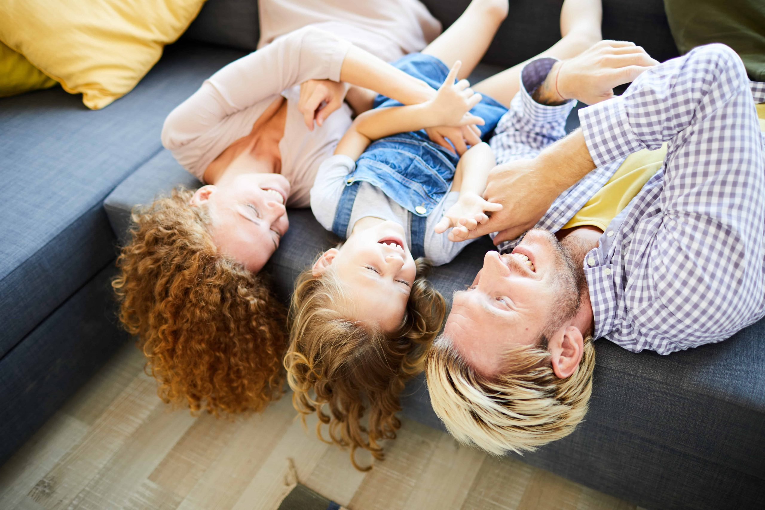 Happy Adoptive family wrestling around on couch