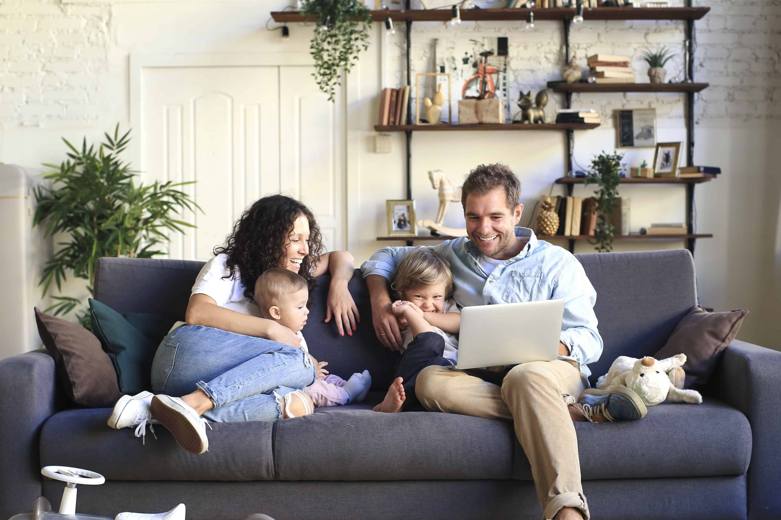 Happy Young adoptive Family enjoying each other on couch